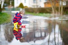 Kleinkindjunge, der mit Papierboot durch Pfütze spielt lizenzfreie stockfotografie