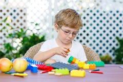 Kleinkindjunge, der mit Plastikblöcken spielt Lizenzfreie Stockfotografie