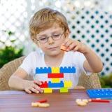 Kleinkindjunge, der mit Plastikblöcken spielt Lizenzfreies Stockfoto
