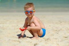 Kleinkindjunge, der mit Schaufel und Sand auf Strand spielt Lizenzfreie Stockfotos