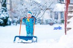 Kleinkindjunge, der mit Schnee im Winter, draußen spielt Stockbild