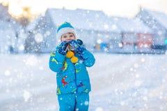 Kleinkindjunge, der mit Schnee im Winter, draußen spielt Stockfotos