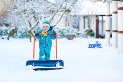 Kleinkindjunge, der mit Schnee im Winter, draußen spielt Stockbilder