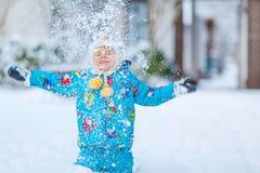 Kleinkindjunge, der mit Schnee im Winter spielt Lizenzfreie Stockbilder