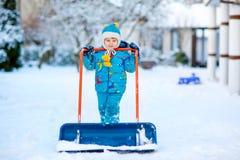 Kleinkindjunge, der mit Schnee im Winter spielt Lizenzfreies Stockfoto