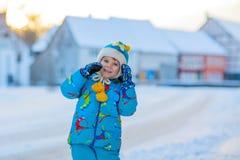 Kleinkindjunge, der mit Schnee im Winter spielt Stockfoto