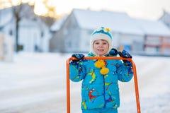 Kleinkindjunge, der mit Schnee im Winter spielt Lizenzfreie Stockfotos