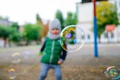 Kleinkindjunge, der mit Seifenblasen spielt Stockbilder