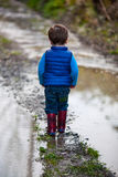Kleinkindjunge in der Pfütze lizenzfreie stockfotografie