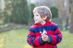 Kleinkindjunge in der roten Jacke, die Schneeglöckchen hält, blüht Lizenzfreies Stockbild