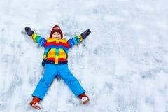 Kleinkindjunge, der Schneeengel im Winter, draußen macht Stockfoto
