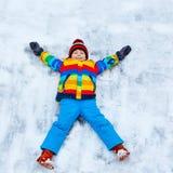Kleinkindjunge, der Schneeengel im Winter, draußen macht Lizenzfreies Stockbild