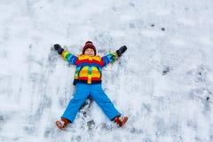 Kleinkindjunge, der Schneeengel im Winter macht Lizenzfreie Stockfotografie