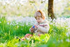Kleinkindjunge, der Spaß mit traditioneller Ostereijagd hat Lizenzfreie Stockfotos