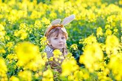 Kleinkindjunge, der Spaß mit traditioneller Ostereijagd hat Stockfotografie