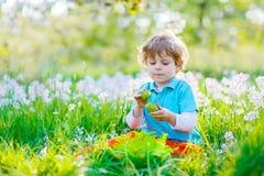 Kleinkindjunge, der Spaß mit traditioneller Ostereijagd hat Stockfoto