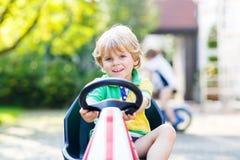 Kleinkindjunge, der Tretauto im Sommergarten fährt Stockfoto