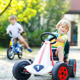 Kleinkindjunge, der Tretauto im Sommergarten fährt Lizenzfreie Stockfotos