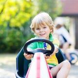 Kleinkindjunge, der Tretauto im Sommergarten fährt Stockfotos
