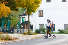 Kleinkindjunge im Sturzhelmreiten mit seinem Roller in der Stadt Lizenzfreie Stockbilder