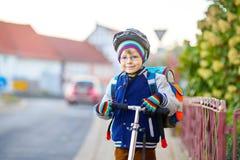 Kleinkindjunge im Sturzhelmreiten mit seinem Roller in der Stadt Stockfotografie