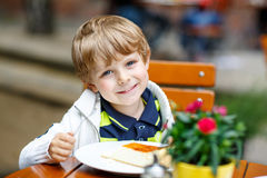 Kleinkindjunge, Kuchen im äußeren Café lachend und essen Stockbild