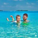 Kleinkindjunge lernt, mit Vater zu schwimmen stockfoto
