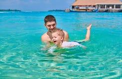 Kleinkindjunge lernt, mit Vater zu schwimmen lizenzfreies stockbild