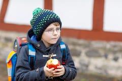 Kleinkindjunge mit Augengläsern gehend von der Schule und Apfel essend Stockfotos