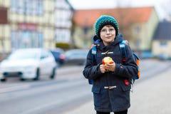 Kleinkindjunge mit Augengläsern gehend von der Schule und Apfel essend Lizenzfreie Stockfotos