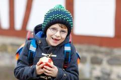 Kleinkindjunge mit Augengläsern gehend von der Schule und Apfel essend Stockfotografie