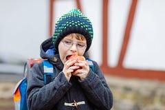 Kleinkindjunge mit Augengläsern gehend von der Schule und Apfel essend Lizenzfreies Stockfoto