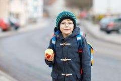 Kleinkindjunge mit Augengläsern gehend von der Schule und Apfel essend Stockfoto