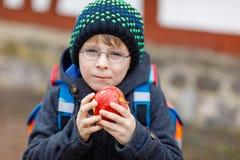 Kleinkindjunge mit Augengläsern gehend von der Schule und Apfel essend Lizenzfreies Stockbild