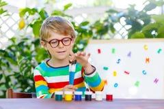 Kleinkindjunge mit den Gläsern, die Schulausrüstung halten Lizenzfreie Stockfotografie