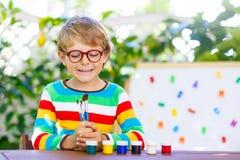 Kleinkindjunge mit den Gläsern, die Schulausrüstung halten Stockfoto