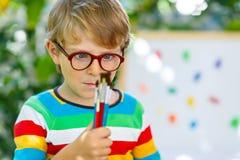 Kleinkindjunge mit den Gläsern, die Schulausrüstung halten Lizenzfreies Stockfoto