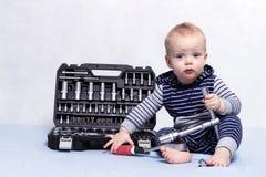 Kleinkindjunge mit Werkzeugkasten und justierbarem Schlüssel in seinen Händen Horizontale Atelieraufnahme Stockfotografie