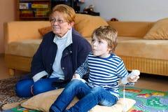 Kleinkindjunge und -großmutter, die Videospielkonsole spielen Lizenzfreies Stockbild
