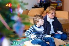 Kleinkindjunge und -großmutter, die Videospielkonsole spielen Stockfoto