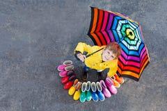 Kleinkindjunge und Gruppe bunte Regenstiefel Blondes Kind, das unter Regenschirm steht Stockfotos
