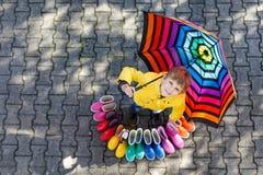 Kleinkindjunge und Gruppe bunte Regenstiefel Blondes Kind, das unter Regenschirm steht Stockbilder