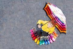 Kleinkindjunge und Gruppe bunte Regenstiefel Blondes Kind, das unter Regenschirm steht Stockfoto