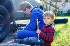 Kleinkindjunge und sein änderndes Rad des Vaters auf Auto Stockbild