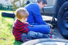 Kleinkindjunge und sein änderndes Rad des Vaters auf Auto Lizenzfreie Stockfotos