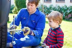 Kleinkindjunge und sein änderndes Rad des Vaters auf Auto Lizenzfreies Stockbild