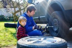 Kleinkindjunge und sein änderndes Rad des Vaters auf Auto Lizenzfreie Stockbilder
