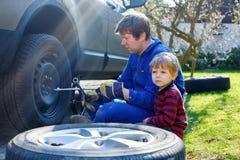 Kleinkindjunge und sein änderndes Rad des Vaters auf Auto Stockbilder