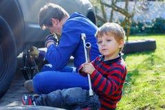Kleinkindjunge und sein änderndes Rad des Vaters auf Auto Lizenzfreie Stockfotografie