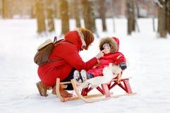 Kleinkindjunge und seine Mutter, die Spaß im Winterpark haben Stockfoto